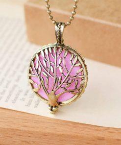 Collar de aromaterapia con fondo rosa de aceite esencial y diseño de árbol